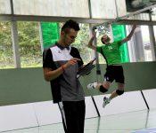 Das Foto zeigt TVA Hürth Volleyballtrainer Cagri Akdogan während Simon Forster im Hintergrund aufschlägt.